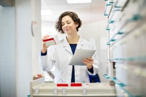 Mulher analisando medicamentos atraves da armazenagem de produtos hospitalares